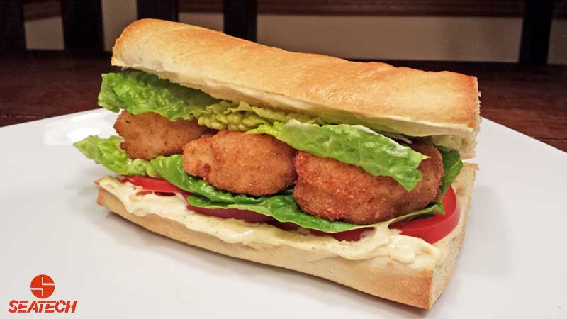 A photograph of an Argentine red shirmp poor boy on fresh french bread with lightly fried shrimp, lettuce, tomatoe mayo and mustard.